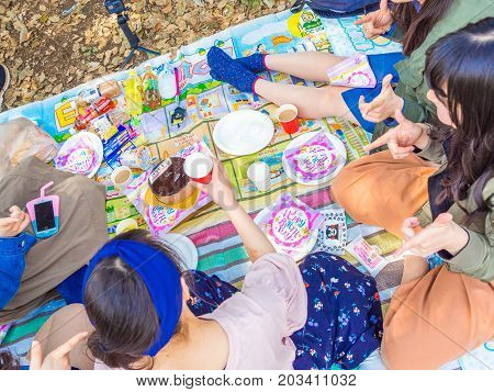 HAKONE, JAPAN - JULY 02, 2017: Unidentified people enjoying the assorted food for lunch in a park in hanami park during cherry blossom season in Kyoto, Japan.