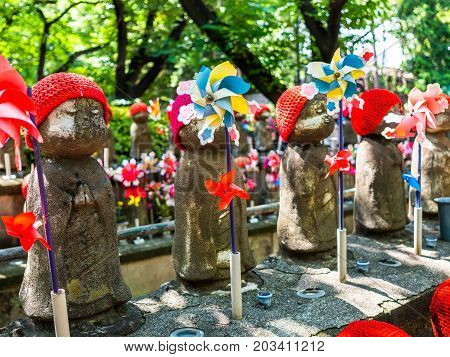 TOKYO, JAPAN - APRIL 5: Jizo Boddhisattvas at Zojo Buddhist Temple at Tokyo, Japan. Jizo Bodhisattva is the patron saint of thechildren's soul according to the Japanese mythology.