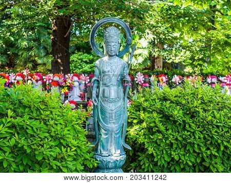 TOKYO, JAPAN - APRIL 5: Close up of a stoned statue with a blurred Jizo Boddhisattvas behind at Zojo Buddhist Temple at Tokyo, Japan. Jizo Bodhisattva is the patron saint of thechildren's soul according to the Japanese mythology.
