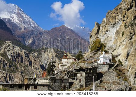 Traditional stone build village of Manang. Mountains in the background. Annapurna region Nepal. Sunny day of Nepal summer. Big mountain stone houses and fresh air. Eco travel
