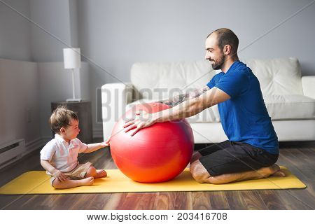 A sports man is engaged in fitness and yoga with a baby at home