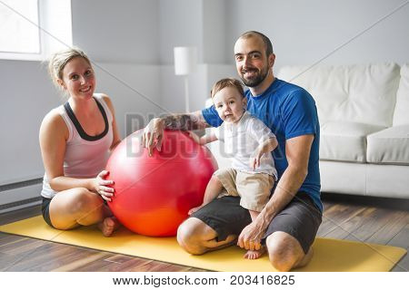 A sports family is engaged in fitness and yoga with a baby at home