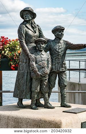 View of The Annie Moore Memorial, statue of Annie Moore and her two Brothers in Cobh, Ireland Annie was the first immigrant to the United States to pass through the Ellis Island facility in New York Harbor