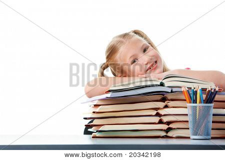 Portrait of cute schoolgirl keeping her arms on open books and looking at camera