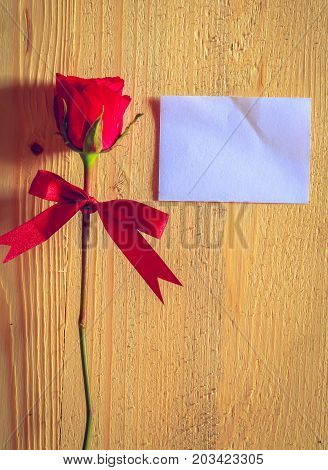 Notebook and red rose flower on wood background