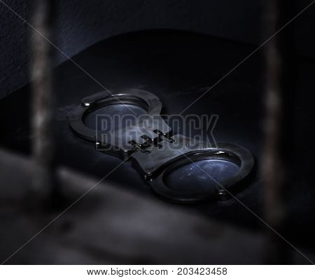 Close up handcuffs on old wooden table background