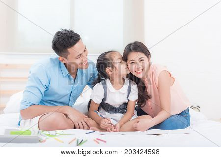 Portrait of happy Asian family. Father daughter kissing mother in bedroom.