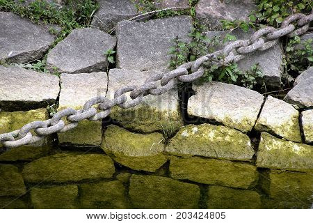 weathered iron chain stretched over layered rocks with green algae