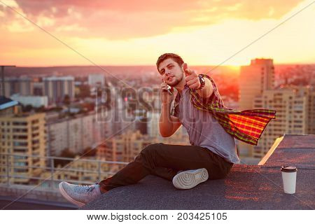 Hipster man talking on his cell phone. He sits on the roof of a high-rise building at sunset. A cup of coffee stands next to him. He points toward the camera