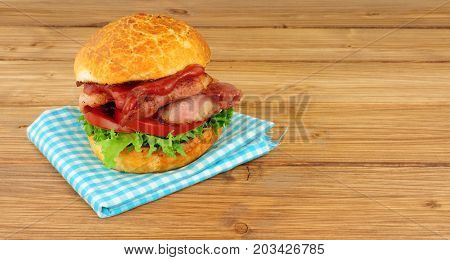 Bacon lettuce and tomato crusty sandwich roll on a wood background