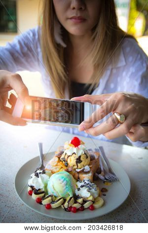 Woman taking picture of Honey Toast and ice cream with smart phone while sitting in coffee shop on summer. girl hand holding take a photo on food using mobile phone. Dessert or food social media photograph hobby. Smartphone or mobile phone photography hab