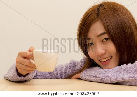 Woman wearing purple warm knitted sweater caucasian young girl holding coffee mug with smiling face on tea time. happy lifestyle. Closeup of Positive Young Pretty Woman with Mug