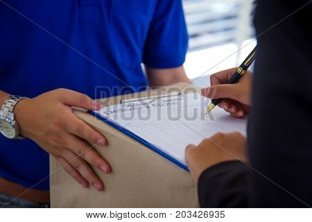 Close up Delivery man in blue uniform holding package while woman is signing receiving documents. Delivery man delivering parcel boxes to a woman customer.