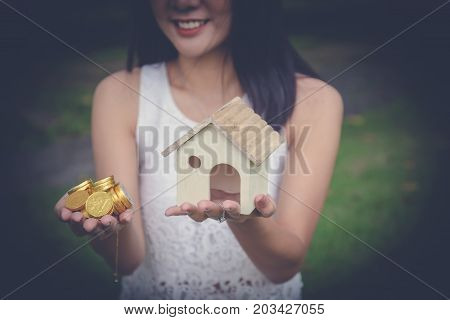 money cash and a model home in woman hands. Young lady hands holding Little house toy and pile of golden coins in outdoor park - property mortgage real estate loan sell owner value concept