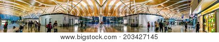 Shanghai, China - Nov 6, 2016: Panorama of the interior check-in area of Shanghai Pudong International Airport. This is a modern facility. People walking about the compound.