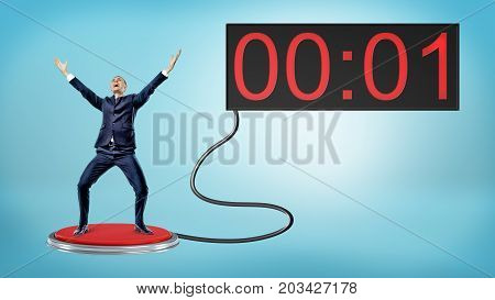 A victorious businessman on a large red push button connected to a screen with one remaining second. Just in time. Last chance. Corporate savior.
