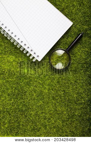 Notebook And Magnifier  On The Grass