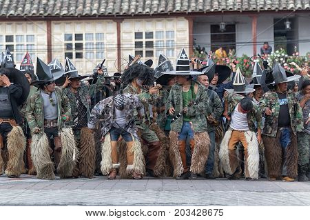 June 24 2017 Cotacachi Ecuador: indigenous kichwa men wearing chaps dancing in the street at the Inti Raymi parade at summer solstice