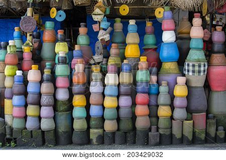 Colorful clay pots on the ground. Tourist art and craft market. Ubud in Bali Island Indonesia. Close up