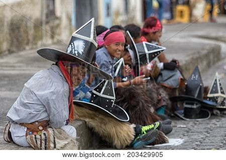 June 24 2017 Cotacachi Ecuador: indigenous kichwa men sitting on the sidewalk tired after participating in a parade at summer solstice