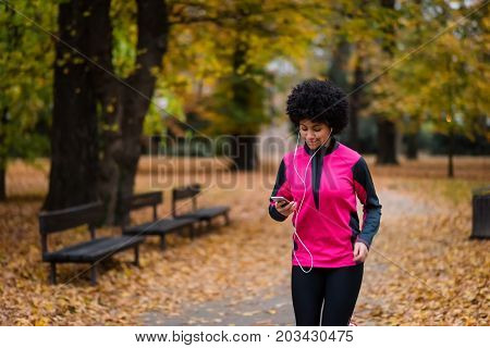 Young woman enjoying music while running in sports apparel