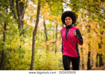 Fitness woman jogging in an autumn park