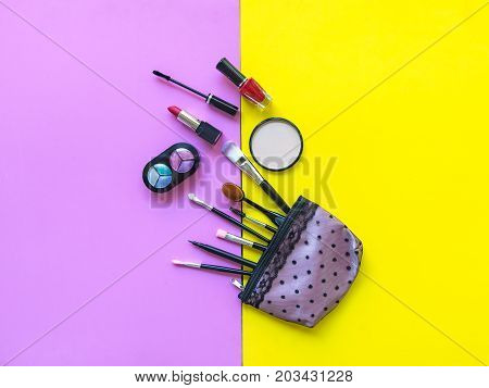Cosmetics and fashion background with make up artist objects: lipstick eye shadows mascara eyeliner concealer nail polish. Pink and yellow colorfull Background. Lifestyle Concept