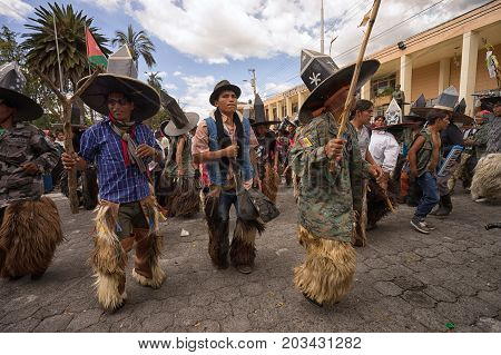 June 24 2017 Cotacachi Ecuador: a group of indigenous kichwa men dancing at the Inti Raymi parade at summer solstice