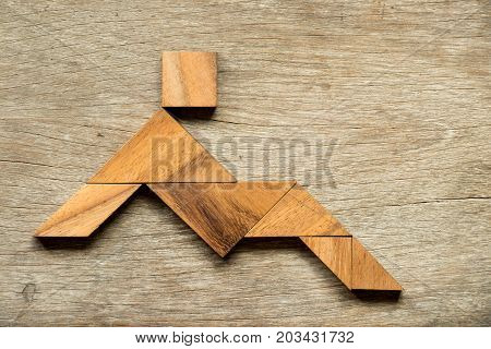 Wood tangram puzzle as man sit or lay down background