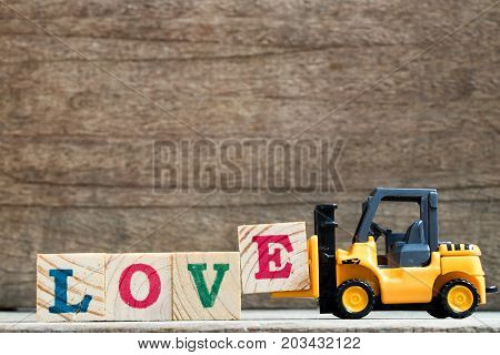 Toy plastic forklift hold block E to compose and fulfill wording love on wood background