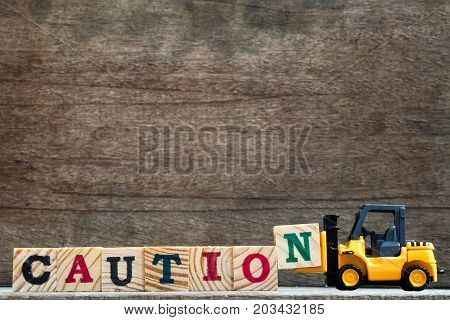 Toy plastic forklift hold block N to compose and fulfill wording caution on wood background