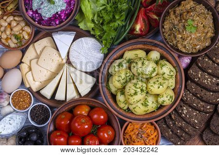Assorted food on wooden background. Boiled young potatoes beans braised cabbage beet salad with cottage cheese sliced cheeses pickled tomatoes korean carrot black bread with seeds green lettuce leaves spice. Bowls and plates with ukrainian food