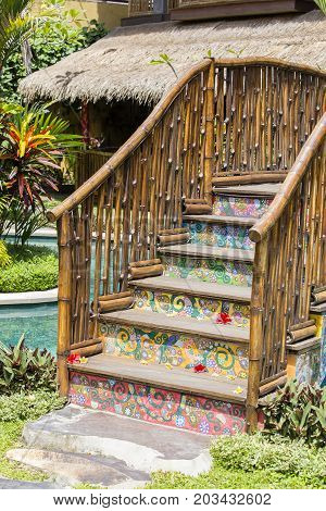 Colorful wooden bridge with bamboo railing in a tropical garden next to the swimming pool in Ubud island Bali Indonesia