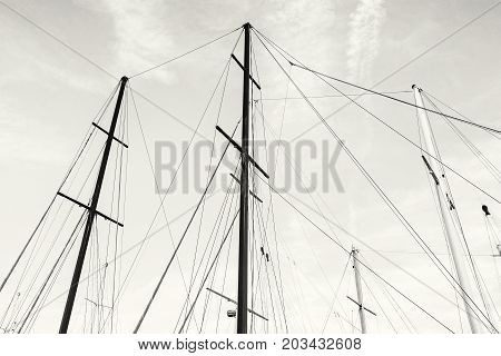 Masts of sailboat and blue sky. Summer vacation. Transport theme. Black and white photo.