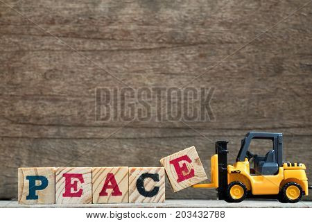 Toy plastic forklift hold block E to compose and fulfill wording peace on wood background