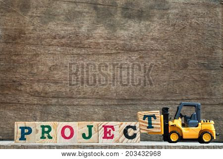 Toy plastic forklift hold block T to compose and fulfill wording project on wood background