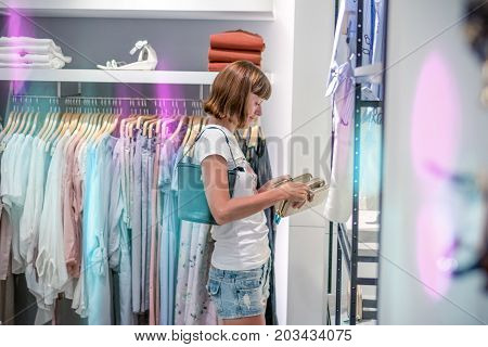 Woman In A Clothing Store Choosing Her New Purse. Shopping Concept. Bali Island. Shopping Mall.