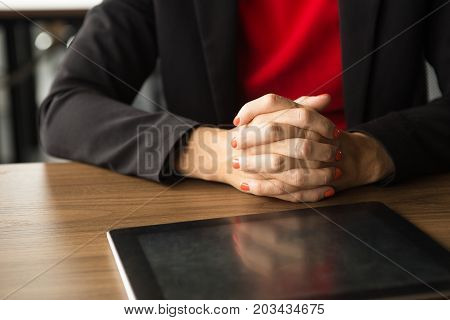 Close-up of clasped hands of businesswoman sitting at table and digital tablet