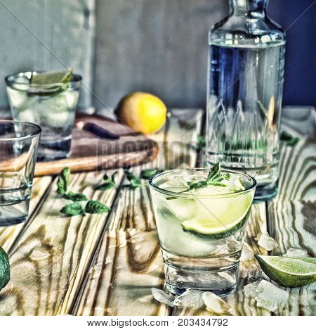 Toned image. Vodka, tequila, gin. Alcoholic cocktail with ice and lime or lemon. wooden floor