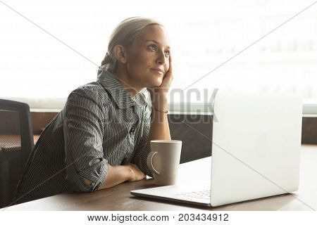 Portrait of dreamy young Caucasian businesswoman sitting in office or woman working in cafe and dreaming