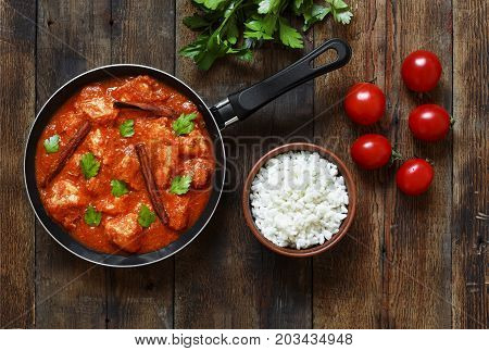 Chicken Curry with butter in a frying pan and a bowl of rice on a wooden table. A few tomatoes and a bunch of cilantro. Traditional Indian food or Pakistani food