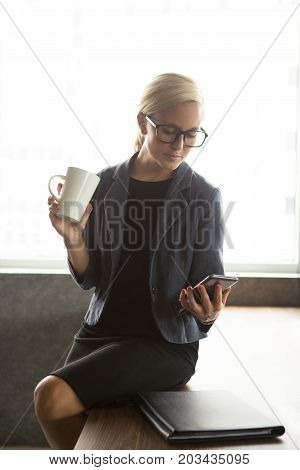 Portrait of serious young Caucasian woman wearing glasses and formalwear sitting on table, drinking coffee and reading message on mobile phone