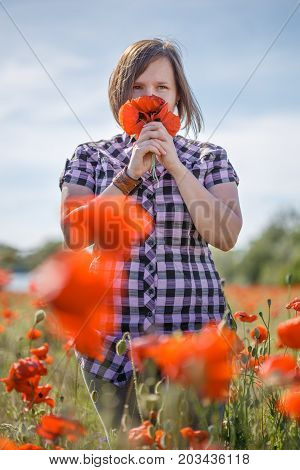 Woman On Flower Field Sniffs Bunch Of Poppies