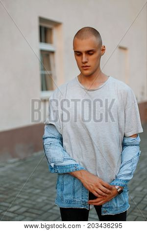 Handsome Young Man In A Gray Shirt And A Denim Jacket On The Street
