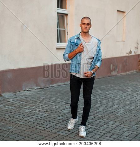 Stylish Young Man In A Denim Jacket, A Gray T-shirt And Black Jeans In White Shoes On The Street