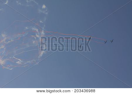 Beautiful acrobatics show of a group of gliders in a sunny sky. Draw colorful loops in the sky.