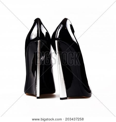 Black lacquered high heel shoes over white
