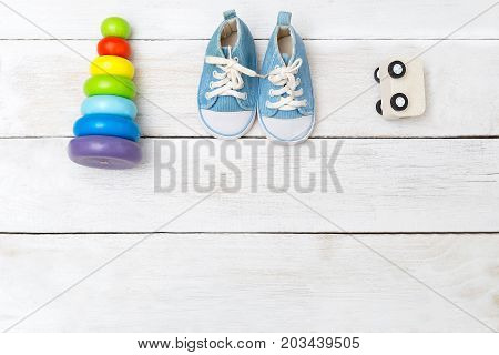 blue baby sneakers and wooden toys. View from above