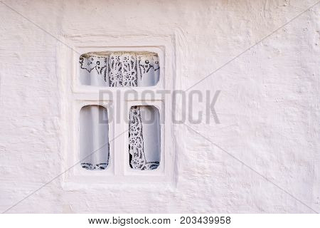 Wall from the whitewashed clay of an old house for habitation with a thatched roof and rounded windows in rectangular black frames with shutters