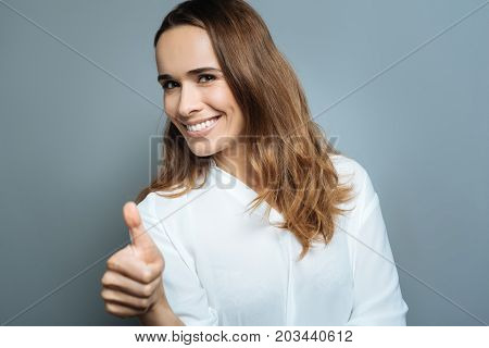 Stay positive. Joyful nice positive woman smiling and showing thumbs up gesture while feeling optimistic